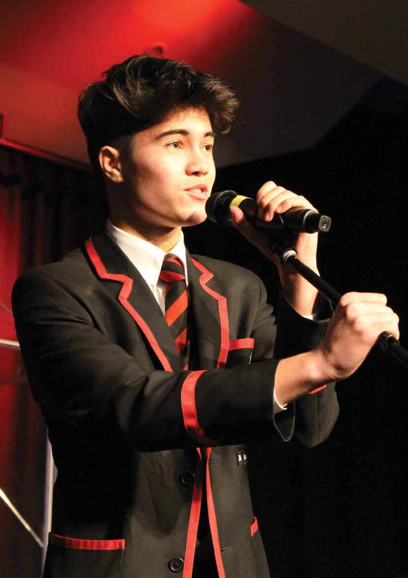 St Bede's College student singing into microphone