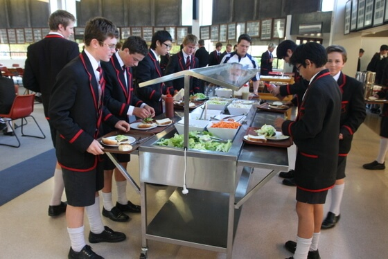 St Bede's College students in large dining hall dishing up food from bain maries