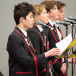 St Bede's College students singing into microphones